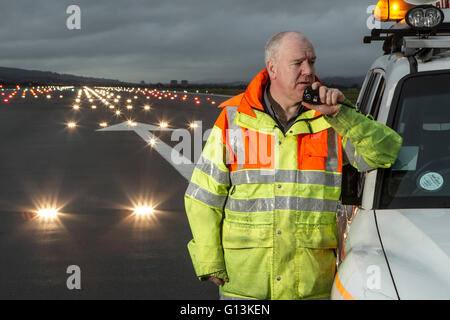 Ground Crew on runway at Glasgow Airport with landing lights in background - Stock Photo