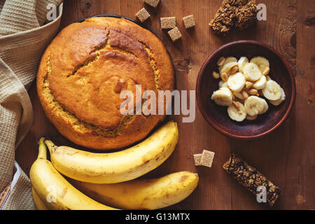 Round loaf of freshly baked banana bread with peanuts, dark chocolate and brown sugar on wooden backdrop. Table - Stock Photo