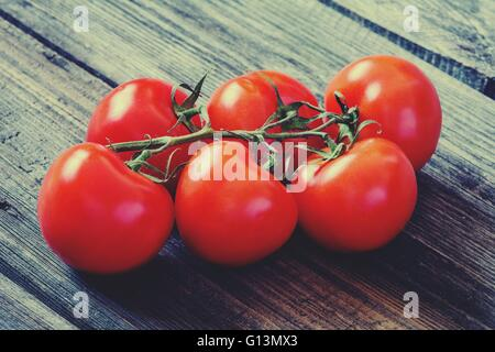 Fresh tomatoes on vine one wooden table. Toned image - Stock Photo