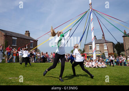 Children dance around a maypole at Aldborough May day festival in North Yorkshire, UK. - Stock Photo