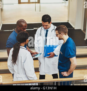 Multiracial group of doctors in an impromptu meeting standing on a stairwell looking at information on a tablet - Stock Photo