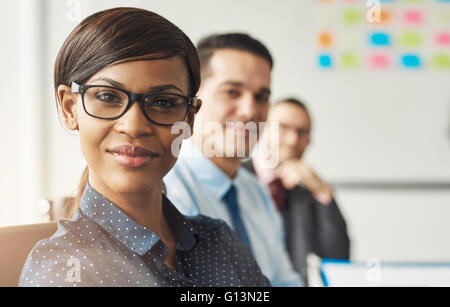 Beautiful smiling business woman wearing eyeglasses and white polka dotted shirt seated with male co-workers at - Stock Photo