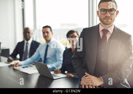 Handsome Caucasian executive with three employees sitting on edge table with back to large bright office window - Stock Photo