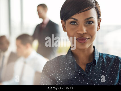 Close up on smiling beautiful business woman with light flare over shoulder from large window in office with group - Stock Photo