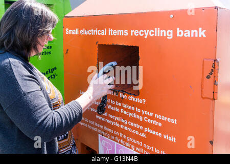 A woman deposits an unwanted electric razor in a small electrical items recycling bank. - Stock Photo