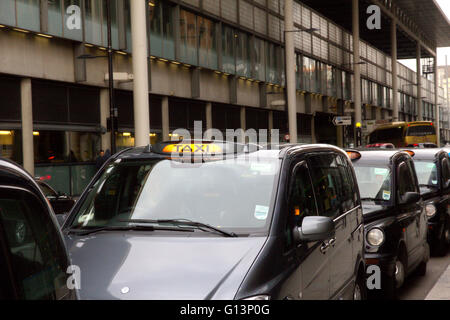A queue of London black cab taxis in a row at a taxi rank, waiting to pick up passengers near Kings Cross station - Stock Photo