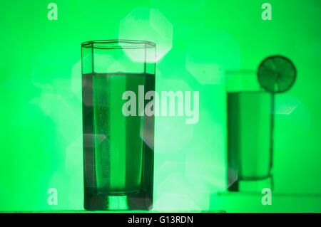 Studio shot of two drinking glasses in the green light and a mirrored lens reflections. Focus on the front glass. - Stock Photo