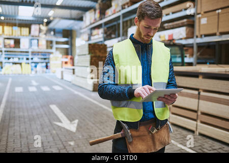 Young warehouse worker dealing in building supplies standing in a drive through consulting a handheld tablet computer - Stock Photo