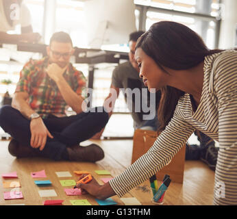 Female business owner writing on various sticky notes for workers on floor in small office with large bright window - Stock Photo
