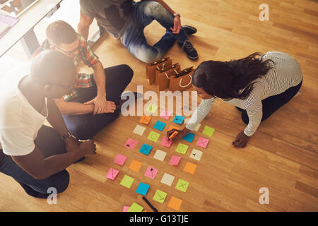 High angle view on female business owner writing on various sticky notes for workers on floor in small office with - Stock Photo