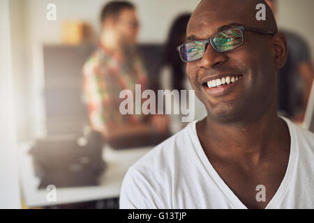 Close up of handsome smiling worker in white shirt and eyeglasses with three out of focus employees behind him in - Stock Photo