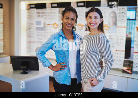 Multiracial entrepreneurs in their shop looking welcoming at camera - Stock Photo