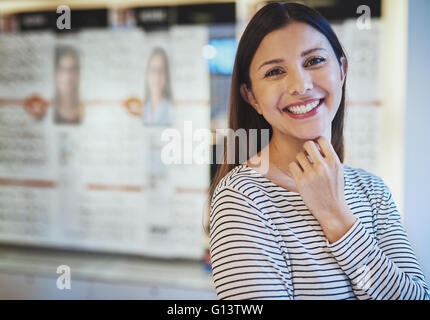 Single beautiful smiling Caucasian woman in striped shirt with fingers under chin in eye wear store - Stock Photo