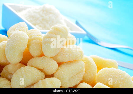 closeup of a pile of gnocchi and a bowl with grated parmesan cheese on a table - Stock Photo