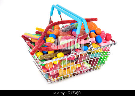 a metal shopping basket full of candies with different shapes and flavors on a white background - Stock Photo