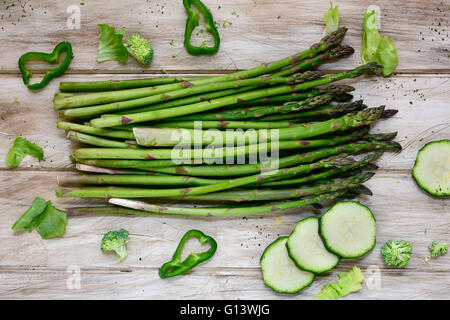 high-angle shot of some different raw green vegetables, such as green pepper, asparagus, broccoli or zucchini, on - Stock Photo