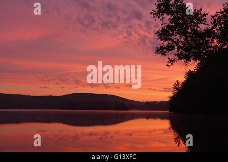Landscape sunrise over a lake in Western Vermont with red clouds - Stock Photo