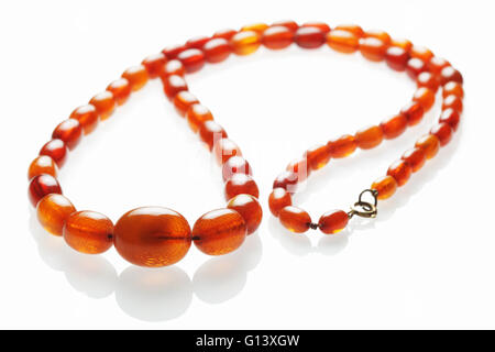 String of antique amber beads for use as a necklace on a white reflecting background - Stock Photo