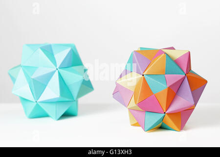 Two colorful modular origami icosahedron folded in paper on a white background. Each module is based on a Sonobe - Stock Photo