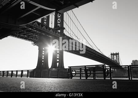 The sun rises under Manhattan Bridge and casts deep shadows on the East River Esplanade - Stock Photo