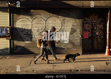 Man with dog on a leash and a girl walk east along Rivington Street on the Lower East Side of New York as the sun - Stock Photo