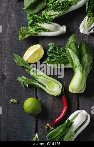 Assortment of whole and sliced raw baby bok choy (Chinese cabbage), red hot chili pepper and lime over old wooden - Stock Photo