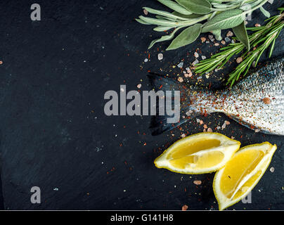 Tail of fresh raw Dorado or sea bream fish on black slate stone board with spices, herbs, lemon and salt. Top view, - Stock Photo