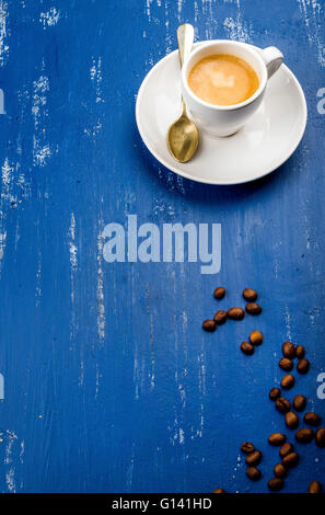 Cup of espresso coffee and beans on wooden blue painted table background. Top view, vertical - Stock Photo