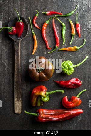 Red and green vegetables and rustic old spoon on dark wooden background, top view. Peppers, chilis and kumato tomatoes - Stock Photo