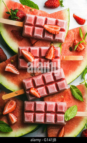 Strawberry watermelon ice cream popsicles with mint over steel tray background. Top view, vertical - Stock Photo