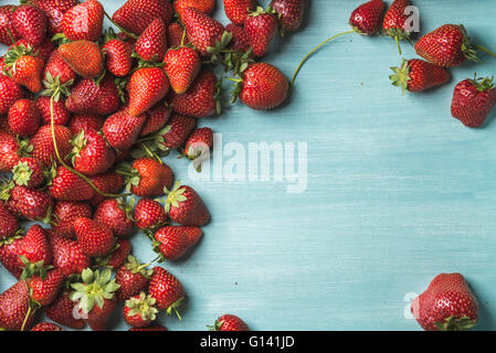 Summer fruit food frame. Strawberries over turquoise blue painted wooden background. Top view, copy space - Stock Photo