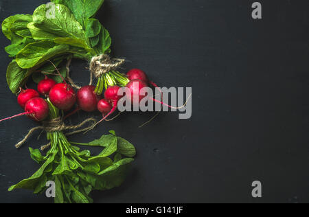 Bunch of radish with leaves on black background, top view, copy space - Stock Photo