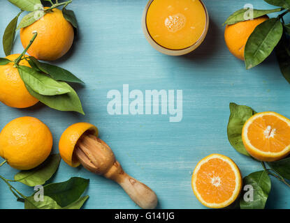 Fresh orange juice in glass and oranges with leaves on wooden turquoise blue painted background. Top view, copy - Stock Photo