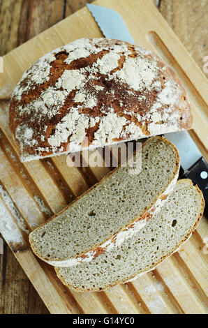 Sourdough rye homemade bread sliced in pieces on a cutting board with a bread knife