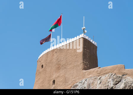 Detail of the medieval Fort Al-Mirani in Muscat, The Sultanate of Oman. The Omani flag in the foreground. - Stock Photo
