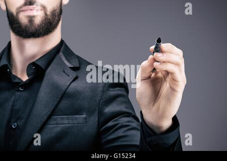 Portrait of a young businessman holding a pen in his hand - Stock Photo