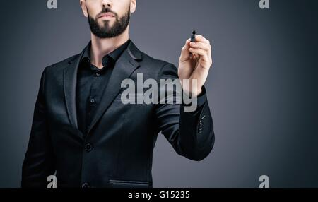 Young businessman holding a pen in his hand - Stock Photo
