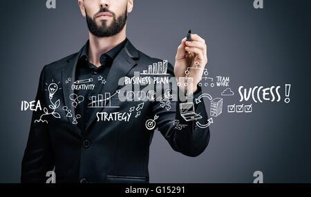 Businessman writing on a virtual table symbols - Stock Photo