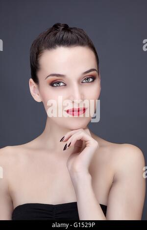 Portrait of a young woman smiling, hand under chin, looking toward the lens - Stock Photo
