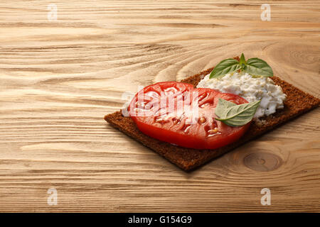 Bread crisp (crispbread open-faced sandwich) with heirloom tomato, cream cheese and fresh basil leaves on wooden - Stock Photo