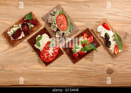 Different bread crisps (crispbread open-faced sandwiches) with both fresh and dried heirloom tomatoes, cream cheese - Stock Photo