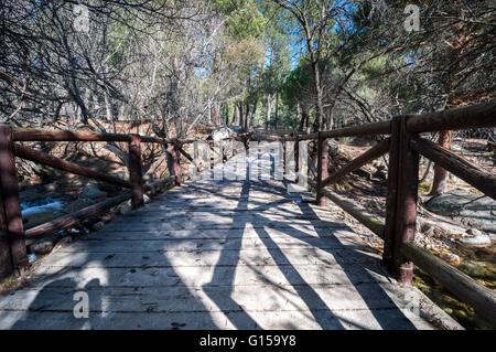 Wooden bridge over the river Manzanares along its course through La Pedriza in Guadarrama Mountains National Park, - Stock Photo