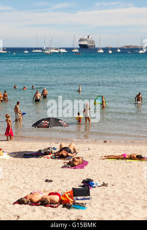 Tourists on a cruise stopover sunbathing on a beach, Calvi, Haute-Corse, Corsica, France - Stock Photo