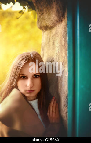young woman standing by the door - Stock Photo