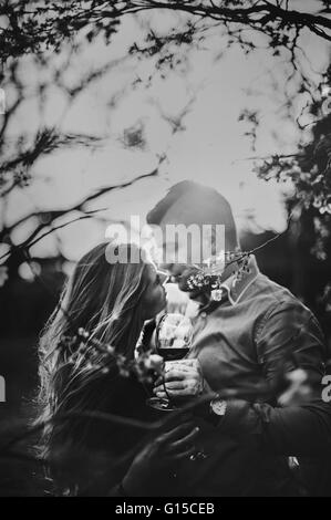young couple embracing  in nature under the tree in spring - Stock Photo