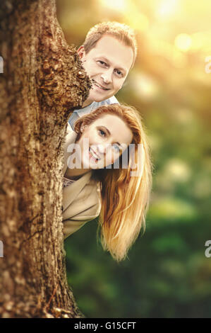 happy young couple standing behind tree and having fun - Stock Photo