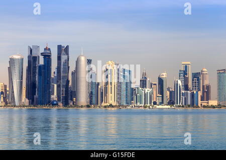 Modern city skyline of West Bay, across the calm waters of Doha Bay, from the Dhow Harbour, Doha, Qatar, Middle - Stock Photo