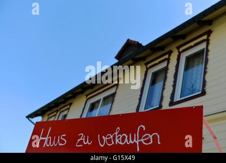 A sign that says 'Haus zu verkaufen' (german, house for sale) stands in front of a house, Germany, city of St. Andreasberg, - Stock Photo