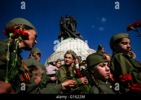 Berlin, Germany. 9th May, 2016. People wearing Soviet army uniforms and holding flowers gather in front of a Soviet soldier statue at the Soviet Memorial in Treptower Park in Berlin, Germany, on May 9, 2016. Peace organizations held on Monday a variety of commemorative activities at a war memorial in Berlin to mark the 71st anniversary of the Soviet victory over Nazi Germany in World War II (WWII). © Zhang Fan/Xinhua/Alamy Live News Stock Photo