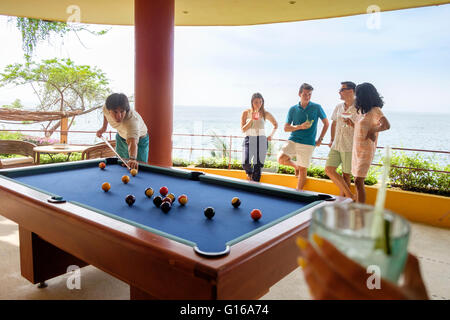 People having cocktail drinks while playing pool billiard on the terrace of an ocean front villa in Mexico - Stock Photo
